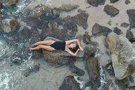 Overhead view of beautiful young woman lying  on rock in the sea - AFVF01753