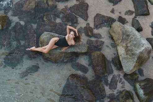 Overhead view of beautiful young woman lying  on rock in the sea - AFVF01756