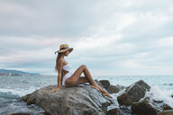 Beautiful young woman wearing swimsuit and hat sitting on rock in the sea - AFVF01765