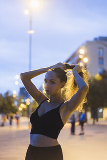 Portrait of beautiful young woman in the city at dusk - AFVF01774
