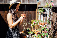 Young woman outdoors, tending to potted plants in garden - ISF19788