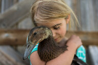 Girl with eyes closed hugging farm duck - ISF19824