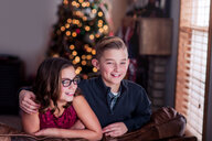 Siblings leaning over sofa, smiling, Christmas tree in background - ISF19827