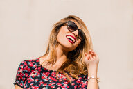 Blond, stylish mid adult woman wearing sunglasses in front of wall laughing - ISF19854