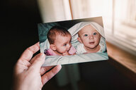 Mother holding photograph of twin baby girl and boy, close up of hand, personal perspective - ISF19857