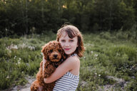 Girl posing with puppy in her arms - ISF19911