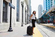 Businesswoman waiting on light rail platform - ISF19935