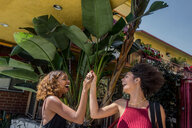 Two young women high fiving outside hotel, Los Angeles, California, USA - ISF19965