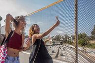 Two young women taking selfie on highway footbridge, Los Angeles, California, USA - ISF19968