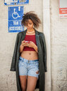 Young woman with leather coat over her shoulders leaning against wall looking at smartphone - ISF19974