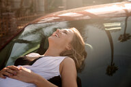 Smiling young woman lying on car bonnet in city - ISF20010