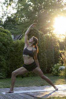 Woman practicing yoga in garden - HHLMF00519
