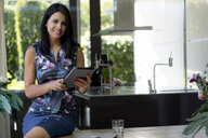 Portrait of smiling dark-haired woman using tablet at home - HHLMF00522