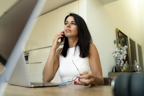 Dark-haired woman on the phone at desk - HHLMF00528