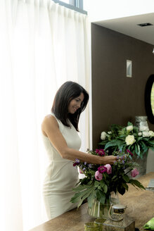 Smiling dark-haired woman arranging flowers at home - HHLMF00534