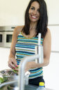Portrait of smiling dark-haired woman preparing saladin kitchen at home - HHLMF00543