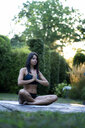Woman practicing yoga in garden - HHLMF00546
