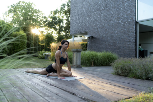 Woman practicing yoga in garden - HHLMF00549