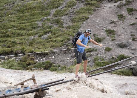 Russia, Caucasus, Mountaineer crossing river in Upper Baksan Valley - ALRF01313