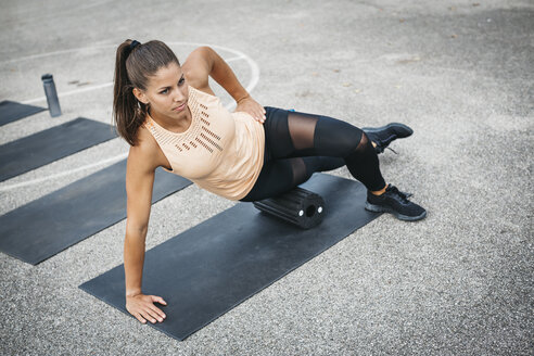 Young woman doing side plank exercise with fascia roll outdoors - HMEF00025