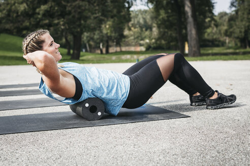 Smiling woman doing workout exercise with fascia roll outdoors - HMEF00028