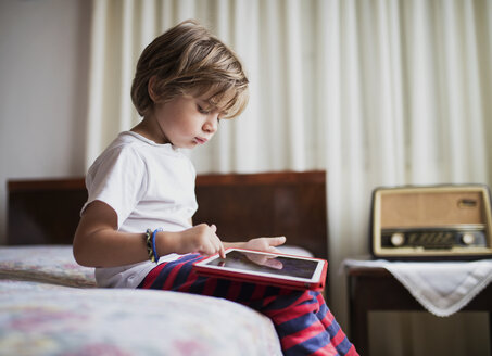 Young boy sitting on bed using a tablet - AZOF00081