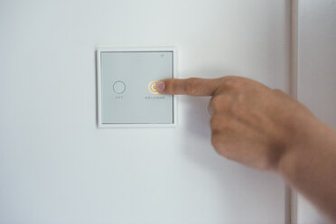 Woman using smart home switch on wall - DIGF05121