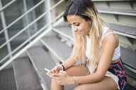 Young woman sitting on stairs, using smartphone - RAEF02152