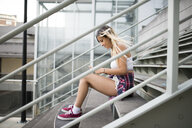 Young woman sitting on stairs, using smartphone - RAEF02155