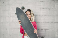 Portrait of a young woman with her long board, in front of a wall - RAEF02170