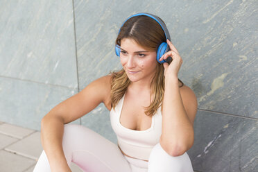 Portrait of smiling young woman listening music with cordless headphones - JUNF01499