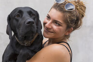 Portrait of happy young woman with her black dog - JUNF01520