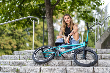 Young woman sitting on stairs with her BMX bike - STSF01763