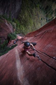 Rock climber climbing sandstone rock, overhead view, Liming, Yunnan Province, China - CUF46060