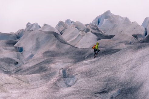 Male hiker hiking over grey snow covered landscape, Narsaq, Vestgronland, South Greenland - CUF46096