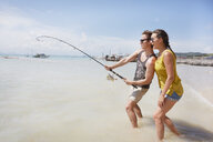 Young couple fishing on beach - LUXF00877