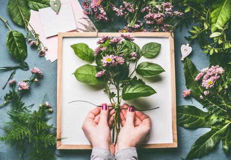 Human hands holding flowering plants - INGF00600