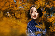 Woman surrounded by a Mimosa tree with shadows on her face - INGF00660