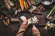 High angle view of human hands preparing food on a cutting board - INGF01146