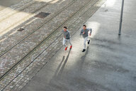 Young adult male twins running together, running along sidewalk, high angle view - CUF46171