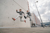 Young adult male twin runners, running and jumping mid air on city sidewalk - CUF46174
