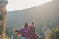 Spain, Alquezar, rear view of two young women on a hiking trip sharing a blanket - AFVF01791