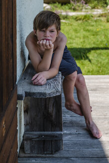 Serious barechested boy leaning on wooden bench in front of a house - HAMF00413