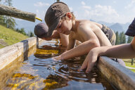 Boys at a well in mountainscape - HAMF00416