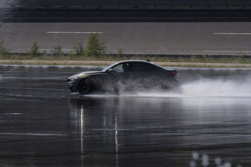 Car driving on wet surface on racetrack - HAMF00440