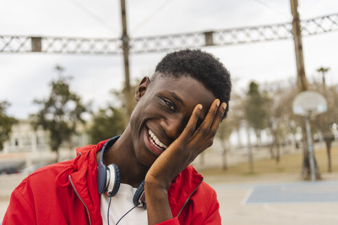 Portrait of a young black man, laughing with hand on his face - AFVF01810