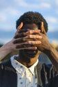 Hands covering eyes of a young black man - AFVF01831