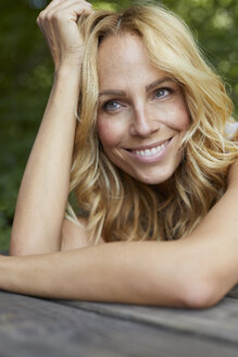 Portrait of smiling blond woman with freckles outdoors - PNEF01005