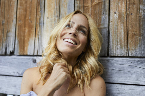 Portrait of happy blond woman in front of wooden wall - PNEF01008