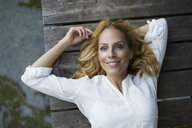 Portrait of smiling blond woman lying on wooden jetty at a lake - PNEF01014